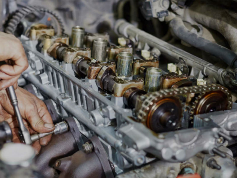 Photo of engine without valve cover showing overhead valves and exhaust manifold.