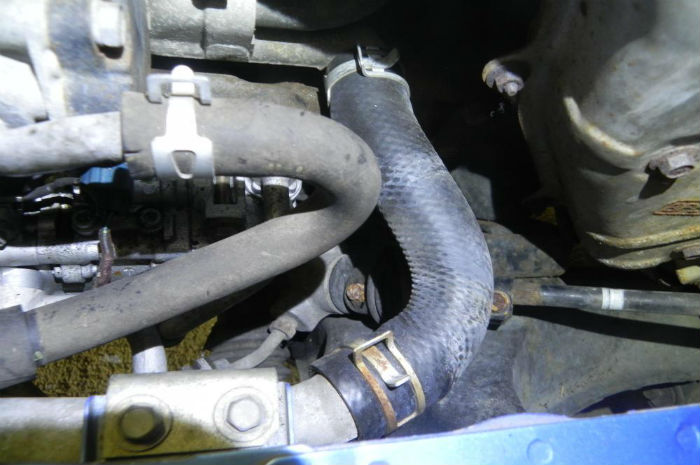 Photo of radiator hose replacement to repair cooling system problem.